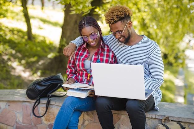公園で勉強している若い抱擁学生 無料写真