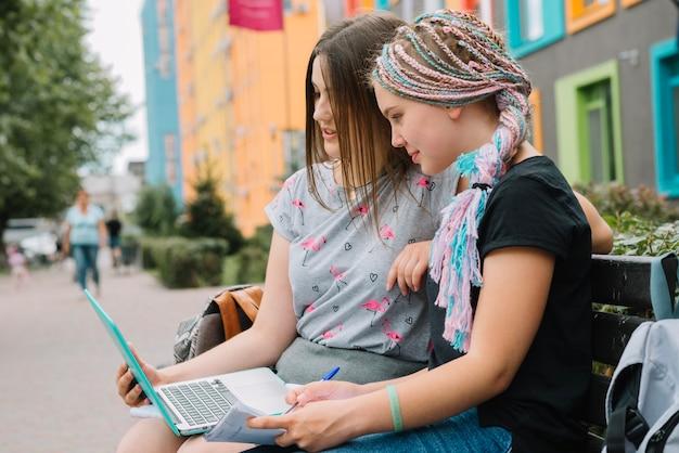 ストリートでラップトップで勉強するスタイリッシュな女の子 無料写真