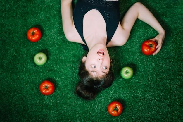 リンゴとトマトの中で驚いた女性 無料写真