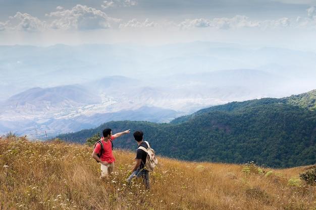 Туристы, указывающие на горы Бесплатные Фотографии