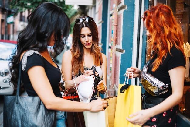 Женщины, показывающие друг другу купленные вещи Бесплатные Фотографии