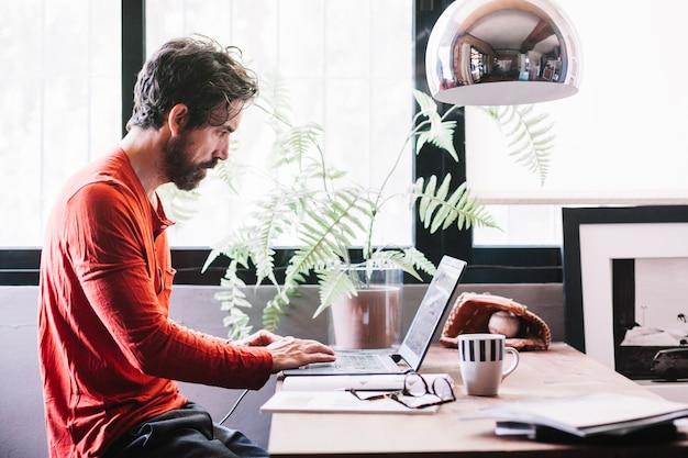家でラップトップで働く男 無料写真