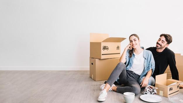 Пара, сидя на полу в новой квартире Бесплатные Фотографии