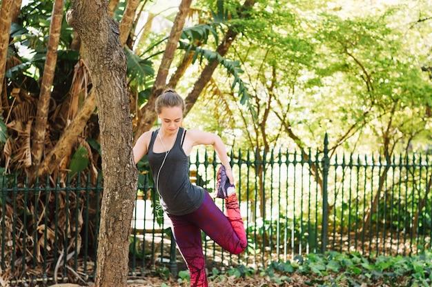 Женщина, растяжение ноги возле дерева Бесплатные Фотографии