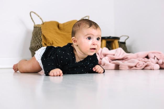床に横たわる愛らしい赤ちゃん 無料写真