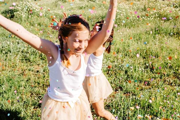 女の子は、色とりどりのシャワーで楽しんでいる 無料写真