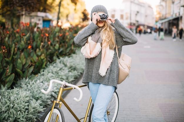 写真を撮っている自転車を持つ女性 無料写真