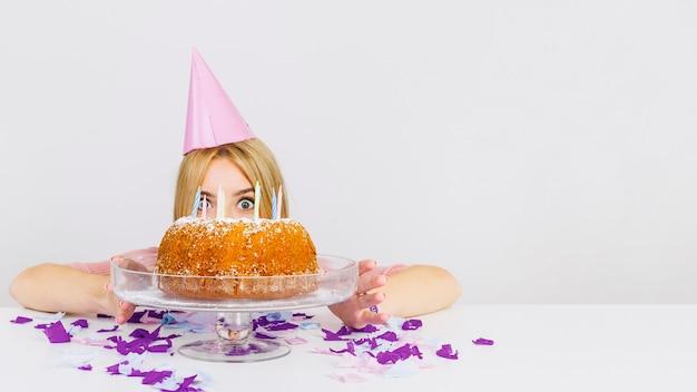 ケーキの後ろに女の顔を持つ誕生日のコンセプト 無料写真