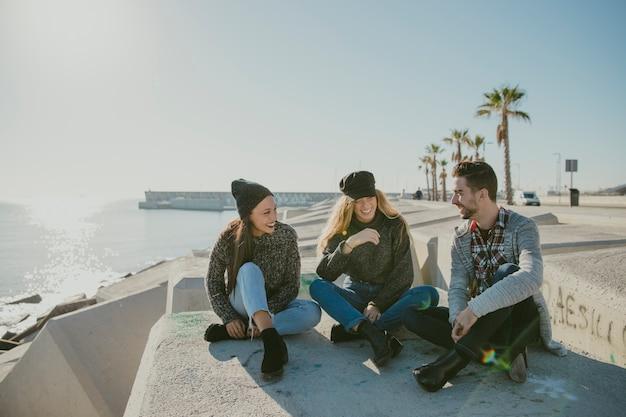 Друзья сидят у моря Бесплатные Фотографии