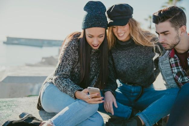Друзья сидят у воды со смартфоном Бесплатные Фотографии