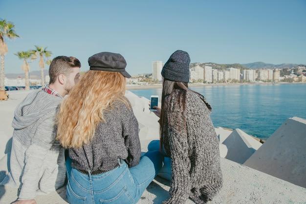 Друзья сидят рядом с водой со смартфоном Бесплатные Фотографии