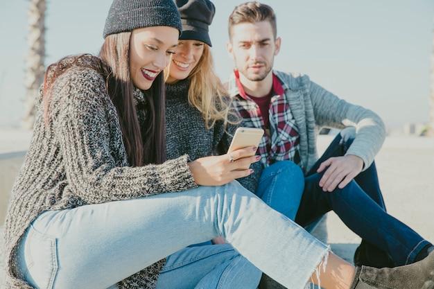 Друзья сидят вместе со смартфоном Бесплатные Фотографии