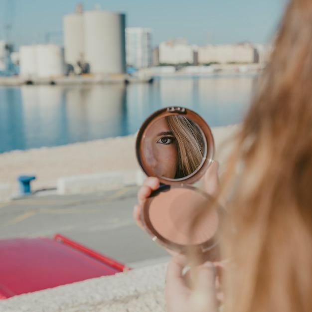 Девушка смотрит в маленькое зеркало перед гаванью Бесплатные Фотографии