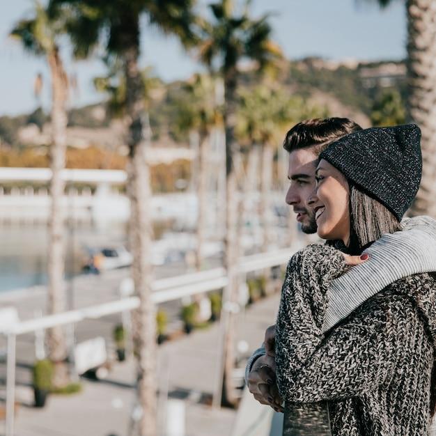 Молодая пара, обниматься перед пальмами Бесплатные Фотографии