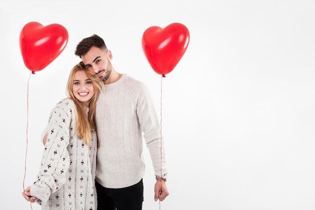 陽気な男と女の風船でポーズ 無料写真