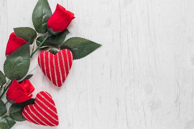 Розы и трикотажные сердца на деревянном фоне Бесплатные Фотографии