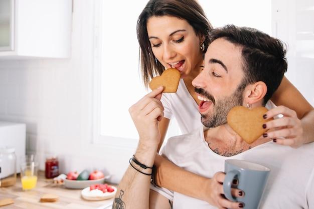 お互いにクッキーを食べるカップル 無料写真