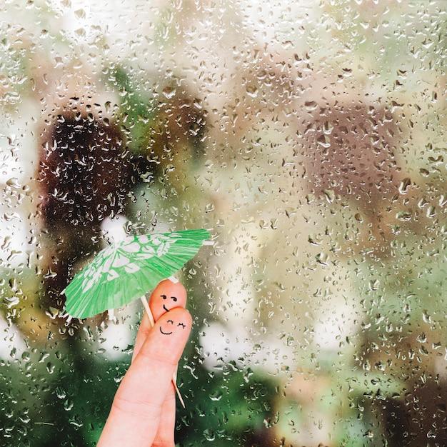 Пальцы с зонтиком возле стекла с каплями дождя Бесплатные Фотографии