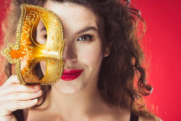 黄金のマスクで笑顔の大人の女性 無料写真