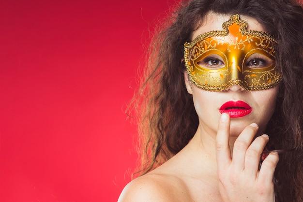 ゴールデンカーニバルマスクの官能的な女性 無料写真