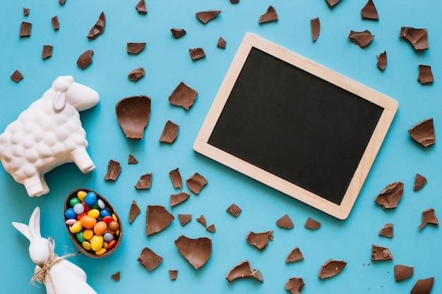 イースターの小像と菓子の近くの黒板 無料写真