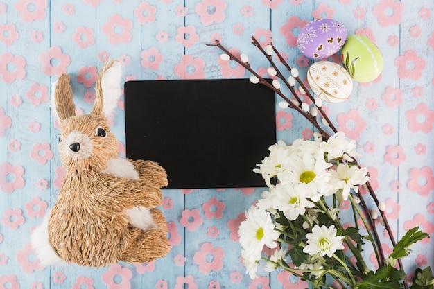 紙の近くに玩具のウサギとイースターのシンボル 無料写真