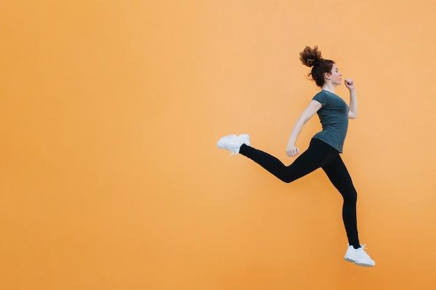 オレンジの壁にジャンプする女性に合う 無料写真