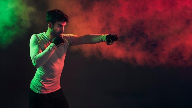 暗闇の中でパンチングする集中ボクサー 無料写真