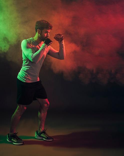 煙で訓練している手袋の中で深刻なボクサー 無料写真
