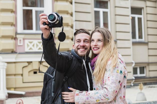 Улыбаясь пара, принимая архитектурные снимки Бесплатные Фотографии