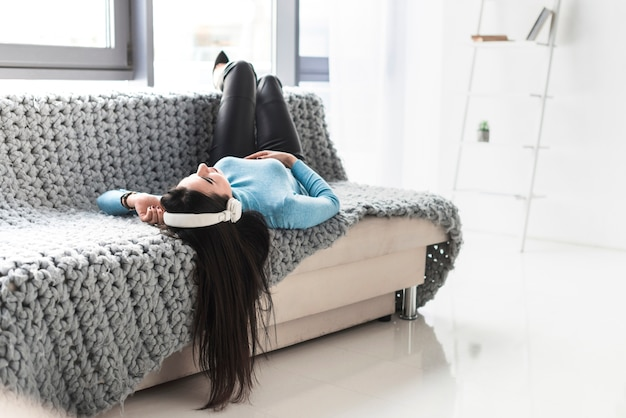 Женщина в наушниках, отдыхающих на диване Бесплатные Фотографии
