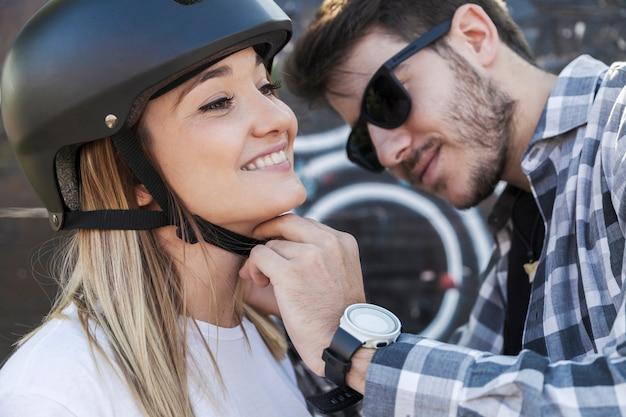 Красивый мужчина, закрепляющий шлем на женщине Бесплатные Фотографии