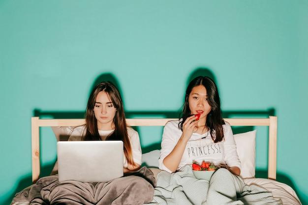 Азиатская женщина ест клубнику возле друга Бесплатные Фотографии