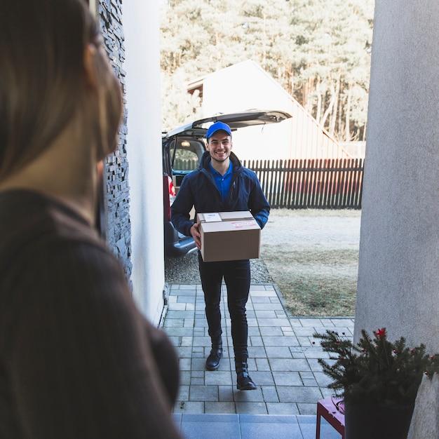 顧客に箱を運ぶ明るい配達人 無料写真