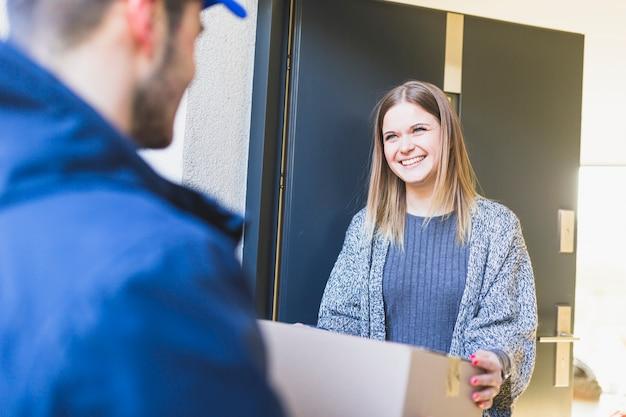 Человек, поставляющий коробку для молодого клиента Бесплатные Фотографии