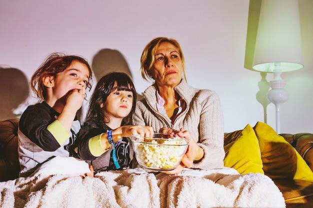 ポップコーンで映画を見ている子供と母親 無料写真