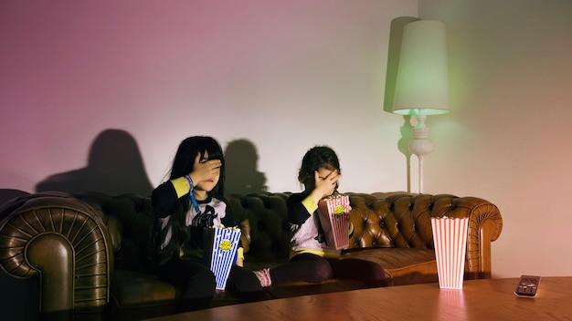 テレビを見ているポップコーンで怖い女の子 無料写真