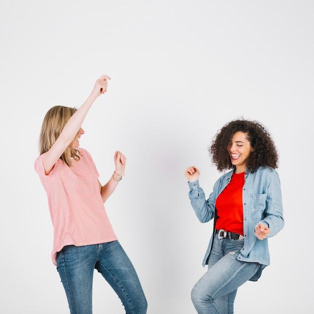 Молодые женщины в стильных нарядах танцуют Бесплатные Фотографии
