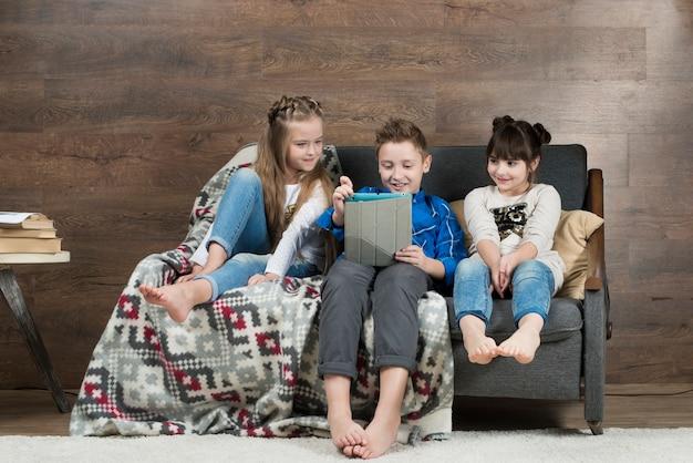 Концепция технологии с детьми на диване Бесплатные Фотографии