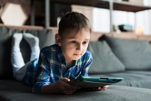 Мальчик, лежащий на диване с планшетом Бесплатные Фотографии