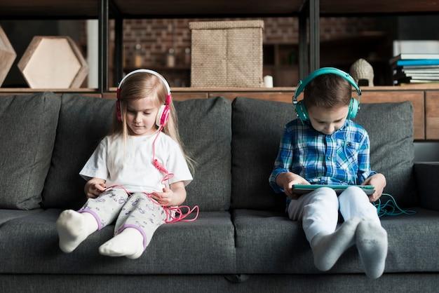 Мальчик и девочка на диване с таблетками Бесплатные Фотографии
