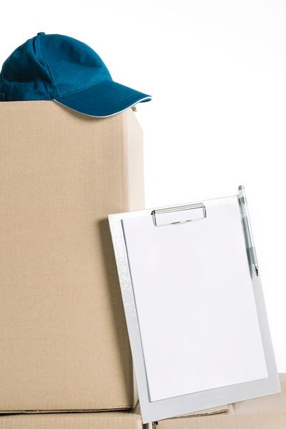 ボックス上のキャップとクリップボード 無料写真