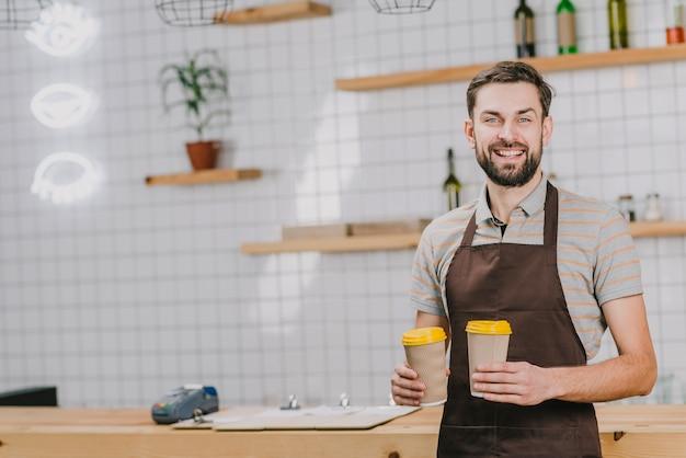 Дружелюбная бариста с чашками Бесплатные Фотографии