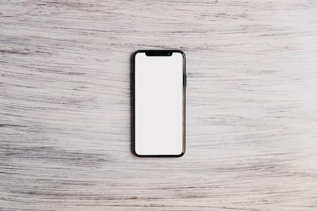 Мобильный телефон с белым белым экраном на деревянной столешнице Бесплатные Фотографии