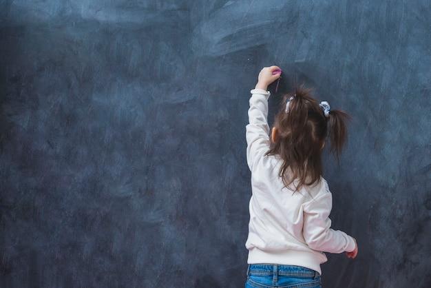 Маленькая девочка делает линию с мелом Бесплатные Фотографии