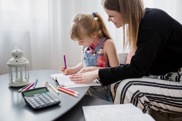 母と娘が一緒に宿題をしている 無料写真