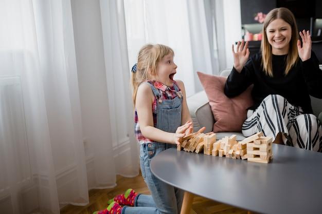 陽気なお母さんと娘、ジェンガを演奏する 無料写真