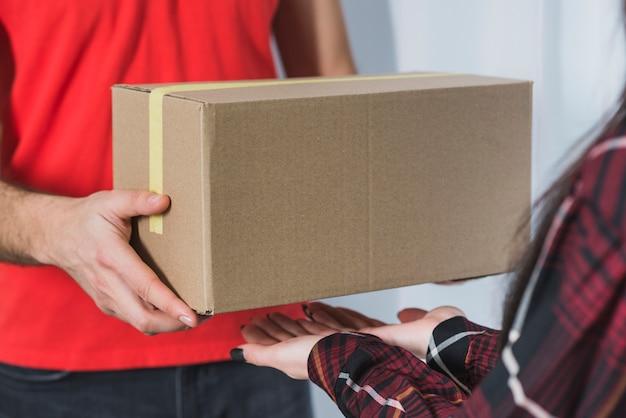 女性に小包を渡す穀物宅配便 無料写真
