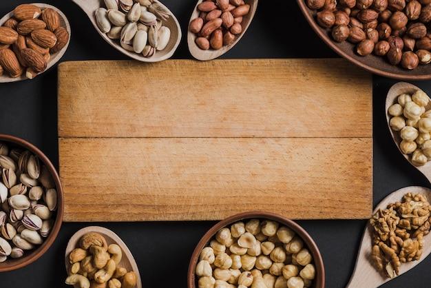 ボードの周りに横たわるナッツのスプーンとボウル 無料写真