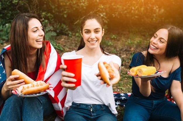 ホットドッグとドリンクを提案する若い女性 無料写真